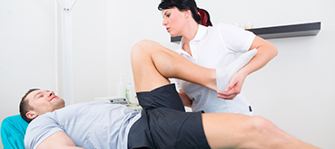 Therapist streching a patient