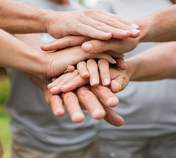 Image: Hands within a group huddle